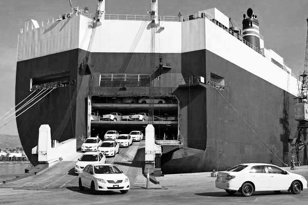 cars unloaded from a vessel in black and white